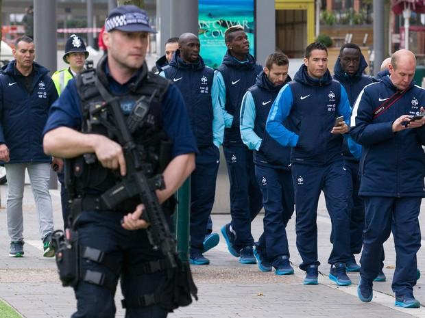 Jogadores e membros da comissão técnica da seleção da França passam escoltados por policiais armados perto do estádio de Wembley, em Londres, antes do amistoso entre Inglaterra e França (Foto: Justin Tallis/AFP)