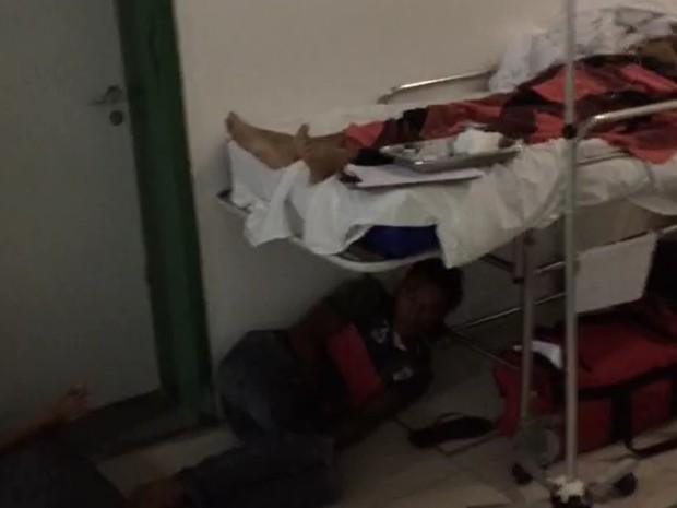 Acompanhante de paciente dorme no chão, sob uma maca, no Hospital Geral de Fortaleza (Foto: TV Verdes Mares/Reprodução)