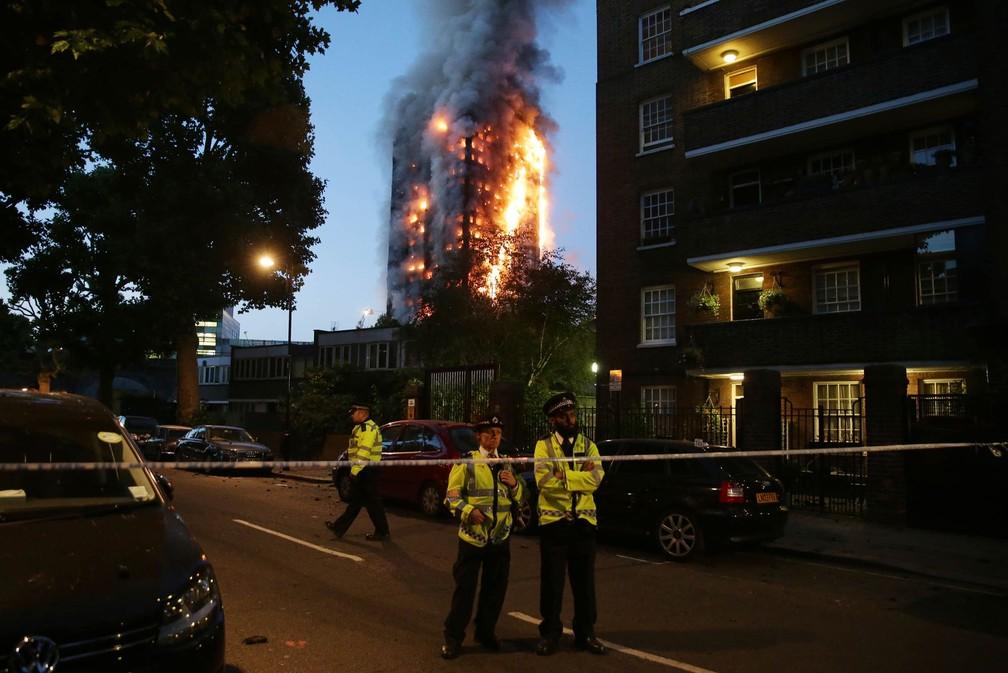 Policiais isolam área próxima ao prédio em chamas durante o amanhecer em Londres (Foto: Daniel Leal-Olivas/AFP)
