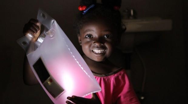 Criança do Haiti com luminária da LuminAid (Foto: Divulgação)