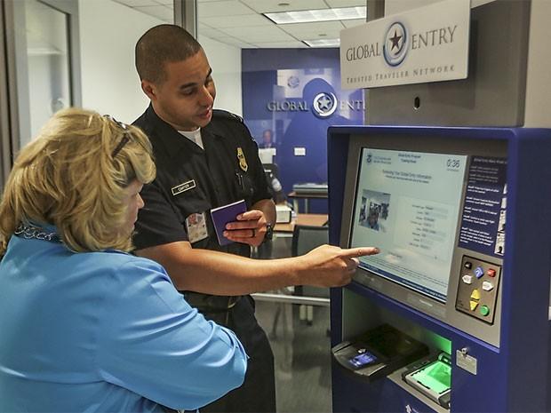 Funcionário da imigração americana explica uso da máquina do sistema Global Entry a usuária (Foto: Divulgação/US Customs and Border Protection/ Josh Denmark)