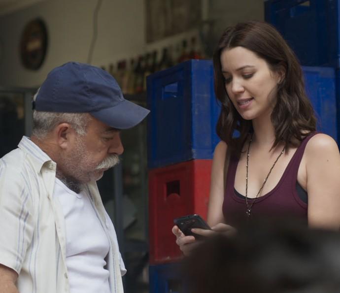 Júlia mostra o celular com foto de Alex a dono de bar (Foto: TV Globo)