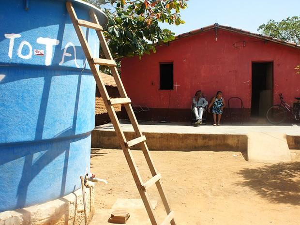 Seu Raimundo e dona Maria têm uma cisterna e uma caixa d'água na porta de casa, mas reclamam que o abastecimento não é regular  (Foto: Anderson Barbosa/G1)