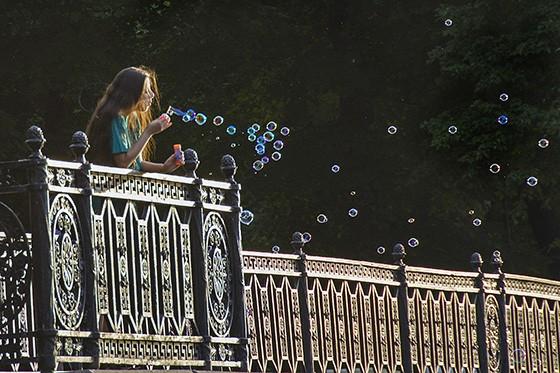 Uma jovem espalha bolhas de sabão em um jardim de São Petersburgo, às margens de um canal  (Foto: © Haroldo Castro/ÉPOCA)