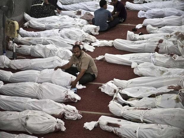15/8 - Egípcios tomam conta dos corpos de familiares e amigos em uma mesquita onde corpos de vítimas da véspera foram reunidos, no Cairo (Foto: Mahmoud Khaled/AFP)