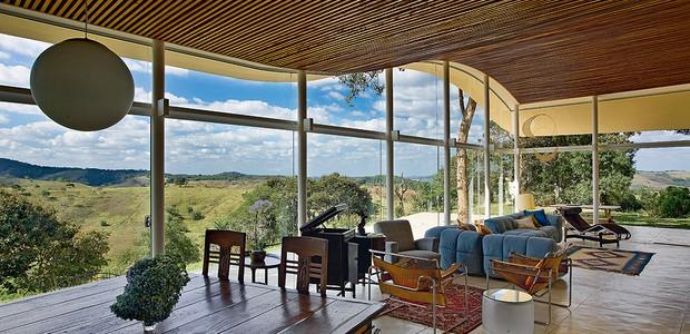 """Na cobertura curva desenhada pelo arquiteto Gustavo Penna se encaixam os painéis de vidro. Não só o living, mas todos os ambientes são integrados à área externa. """"A casa é pequena, mas nela cabe o mundo inteiro que entra pela transparência"""", conclui (Foto: Jomar Bragança/Casa e Jardim)"""