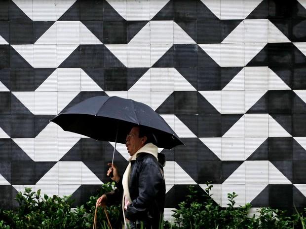 Pedestres se protegem da chuva e do frio na região central de São Paulo. Segundo o Instituto Nacional de Meteorologia a temperatura mínima na capital paulist anesta sexta é de 15ºC e a máxima 19ºC (Foto: Nelson Antoine/Frame/Estadão Conteúdo)
