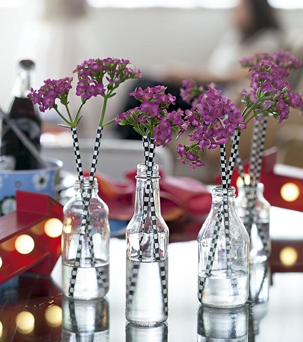 Garrafas transparentes viram vasos de efeito comessa ideia fácil de ser executada: espete as flores em canudinhos estampados. Canudos Shopfesta, luminoso Villa Pano (Foto: Cacá Bratke/Editora Globo)