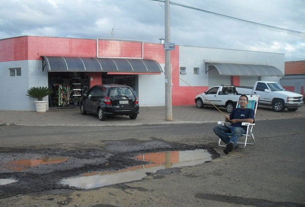 Silva posa para foto em 'pescaria' no buraco de rua em Piracicaba (Foto: Carlos Eduardo da Silva/VC no G1)