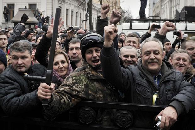 Manifestantes comemoram ações do Parlamento da Ucrânia do lado de fora do local em Kiev neste sábado (22) (Foto: Louisa Gouliamaki/AFP)