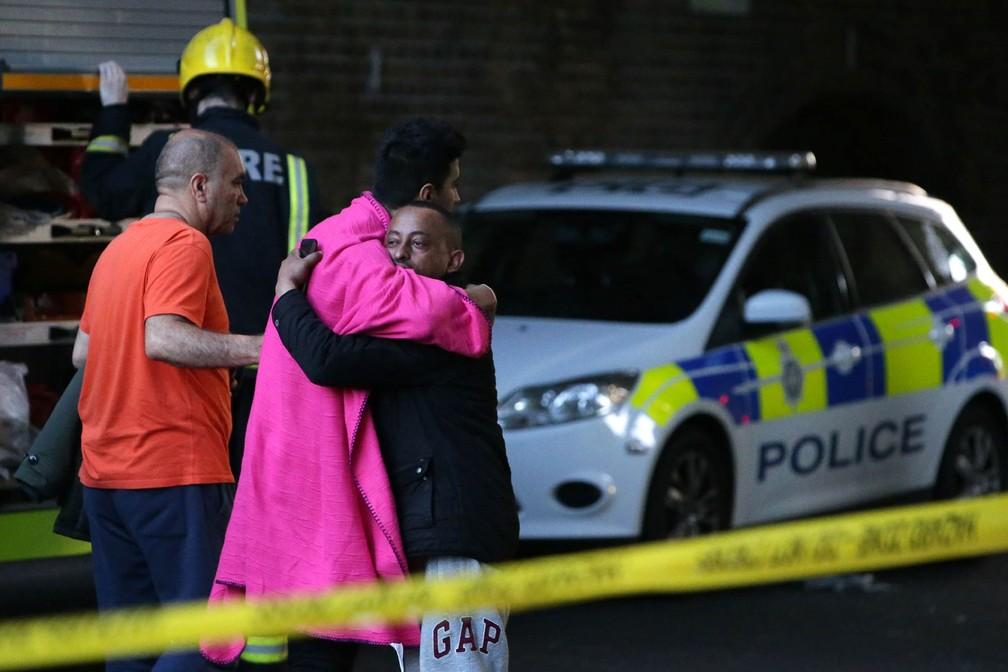Homens se abraçam do lado de dentro do cordão de isolamento policial enquanto o fogo toma conta da Torre Grenfell, em Londres (Foto: Daniel Leal-Olivas/AFP)