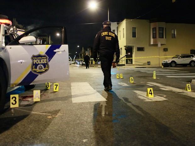 Investigador caminha pelo local onde o policial Jesse Hartnett foi baleado, na Filadélfia, na sexta (8) (Foto: AP Photo/Joseph Kaczmarek)