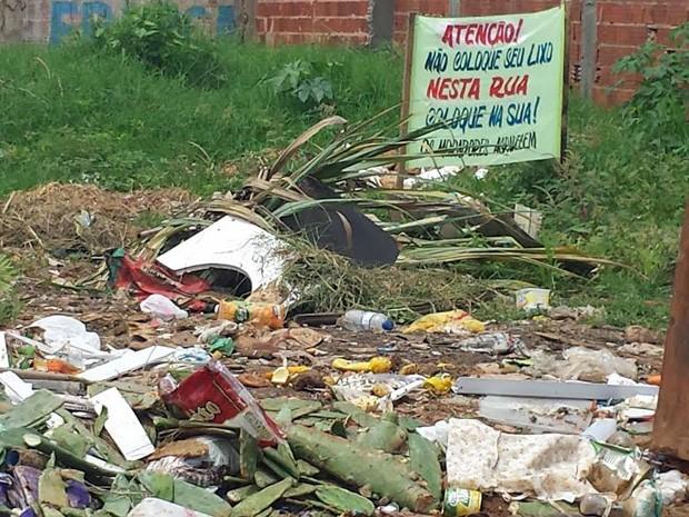 Faixa instalada em terreno vazio no Pôr do Sol pede que moradores não joguem lixo no  local (Foto: Isabella Formiga/G1)