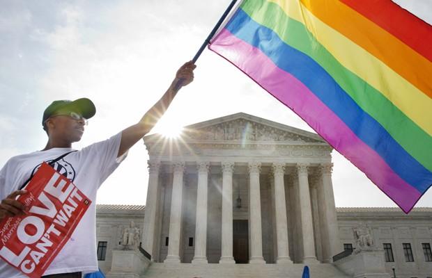 Ativista Carlos McKnight levanta bandeira do movimento GLBT em frente à Suprema Corte em Washington, nesta sexta (26), após a aprovação do casamento entre homossexuais em todo o país (Foto: Jacquelyn Martin/AP)