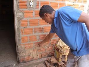 Aldenor mostra a marca da água na parede da casa (Foto: Gustavo Almeida/G1)