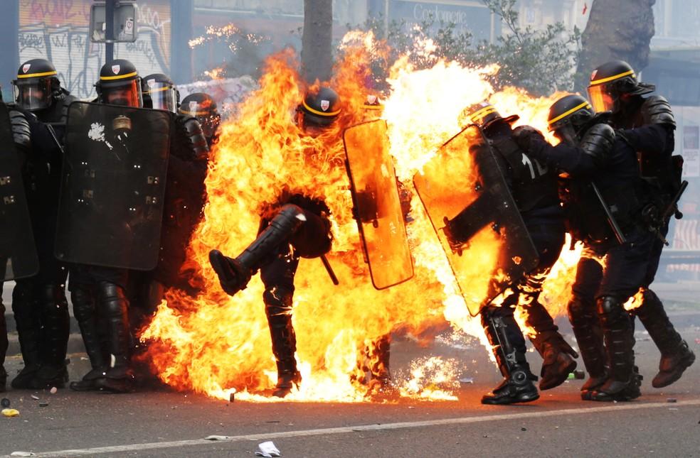 Policial é engolido pelas chamas em protesto em Paris. Neste 1º de maio, seis agentes de segurança ficaram feridos, um deles seriamente, segundo a emissora local BFMTV.  Não há informações específicas sobre o homem da foto. Um protesto no centro da capital francesa teve confronto quando um grupo de mais de cem mascarados se misturou aos demais manifestantes e começou a lançar objetos -- entre eles, coquetéis molotov --contra a polícia, que reagiu com gás lacrimogêneo. (Foto: Zakaria Abdelkaf/AFP)