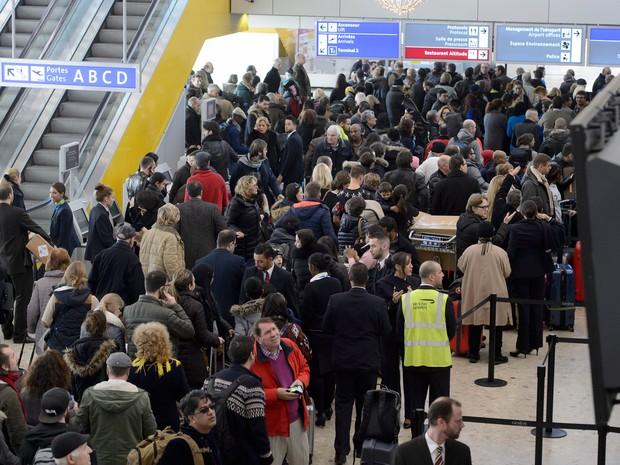 Passageiros aguardam operação da polícia depois que uma mala suspeita foi identificada no aeroporto de Genebra neste sábado (12); dois homens foram presos nesta sexta por suspeita de ligação com terrorismo  (Foto: Richard Juilliart/AFP)