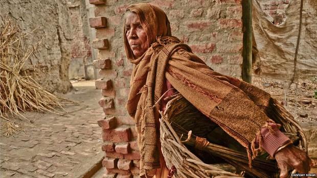 Mulheres das castas mais baixas da Índia, como Gangashree (foto), limpam baneiros de casas sem sistema de descarga moderno: na imagem, ela leva as fezes em seu cesto para os arredores do vilarejo (Foto: Digvijay Singh/BBC)