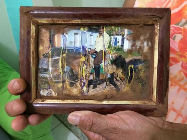 Francisco de Paula Felipe segura uma foto encontrada no meio da lama, em Bento Rodrigues (MG). Ela mostra um ex-morador, José dos Santos, montado em burro (Foto: Reprodução/G1) (Foto: Flávia Mantovani/G1)