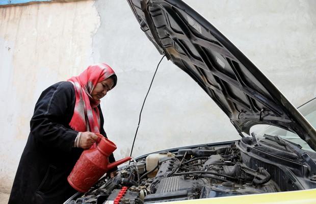 Sara Bahai, de 40 anos, inspeciona condições de seu carro  (Foto: Mustafa Najafizada/AP)