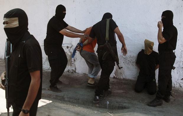Militantes do Hamas cercam palestinos acusados de terem colaborado com Israel nesta sexta-feira(22); 18 foram mortos (Foto: Reuters)