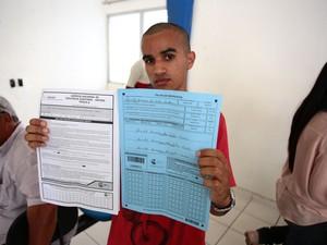Candidato mostra prova e folha de resposta (Foto: Jonathan Lins/G1)