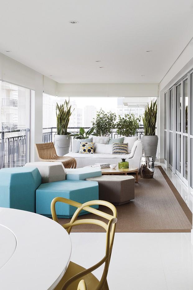 """O projeto da arquiteta Flávia Gerab Tayar para a varanda de 40 m² ficou na medida para o casal de 30 anos, que gosta de design e acabou de ter um bebê. Após fechá-la com painéis deslizantes de vidro ela colocou no meio da área o sofá. """"Como os módulos são soltos, as pessoas ficam livres para sentar em posições diferentes"""", diz ela (Foto: Marcelo Magnani e Maíra Acayaba/Casa e Jardim)"""