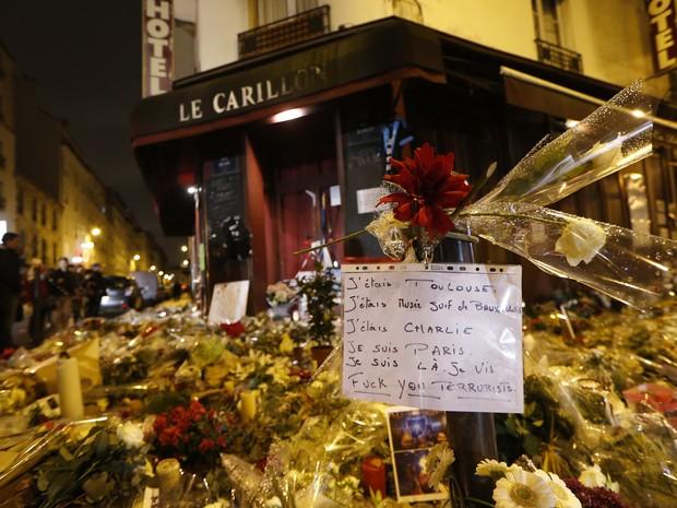 Flores e notas sãos vistas nesta sexta (20) em frente ao café Carillon, na esquina das ruas Bichat e Alibert, em Paris, onde pessoas foram mortas durante ataque terrorista há uma semana (Foto: AFP Photo/Thomas Samson)