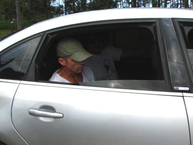 Usando boné, Hudson deixa a Penitenciária 2 de Tremembé (SP) no banco de trás do carro. (Foto: Renato Ferezim/G1)