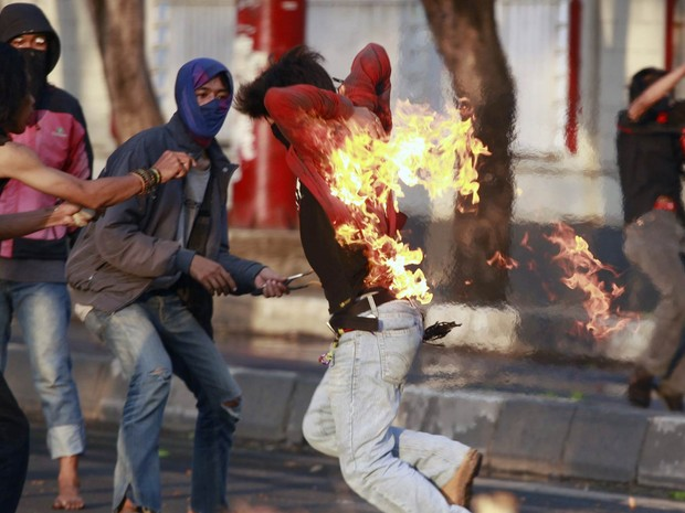 Estudante indonésio corre em desespero com as costas em chamas após suas blusa pegar fogo enquanto acendia um coquetel molotov num protesto em Makassar, Indonésia. Os jovens protestam contra decisão do novo presidente de aumentar o preço dos combustíveis (Foto: Yusuf Ahmad/Reuters)