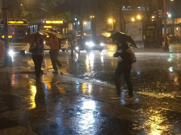Pedestres se protegem da chuva no Centro do Rio (Foto: Daniel Silveira/G1)