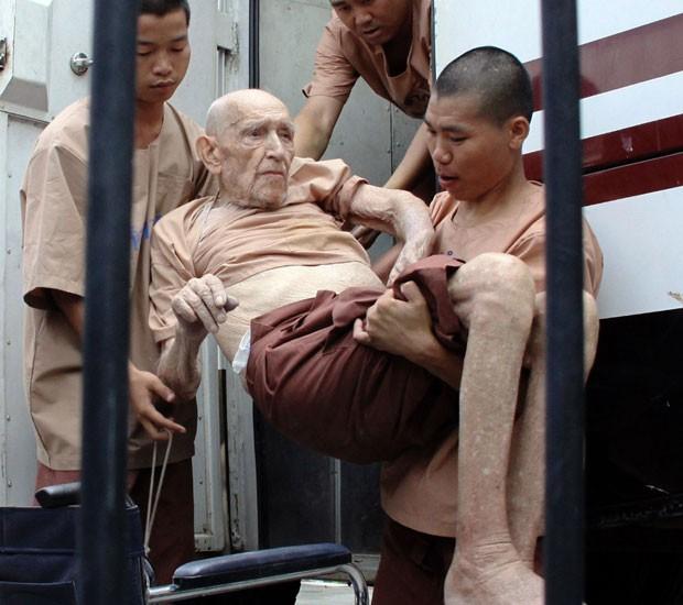 Karl Joseph Kraus, australiano de 93 anos, é carregado por funcionários tailandeses em sua chegada à Corte em Chiang Mai, norte da Tailândia. Kraus foi preso e é acusado de estuprar quatro irmãs de 7 a 15 anos em 2010. (Foto: Wichai Taprieu/AP)