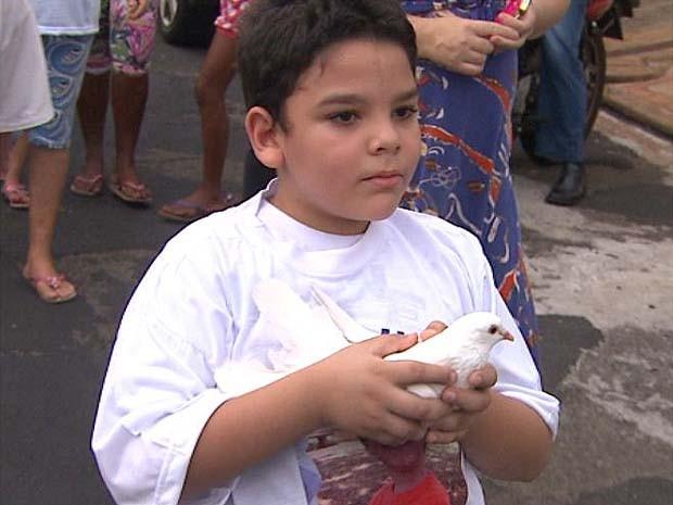 Garoto leva pombo em ato pela paz em homenagem a Joaquim em Ribeirão Preto, SP (Foto: César Tadeu/EPTV)