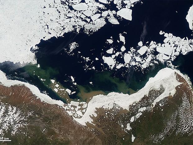 A água do rio Mackenzie, no Canadá, em 14 de junho de 2012, começa a quebrar a geleira no litoral (Foto: Nasa)