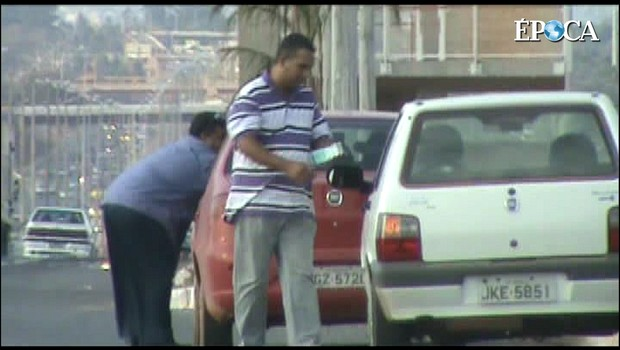 Vídeo mostra gerente de fornecedora do governo do Distrito Federal depositando dinheiro vivo em carro de servidor público. MP suspeita de caixa dois na campanha de Agnelo Queiroz (PT)    (Foto: Reprodução)