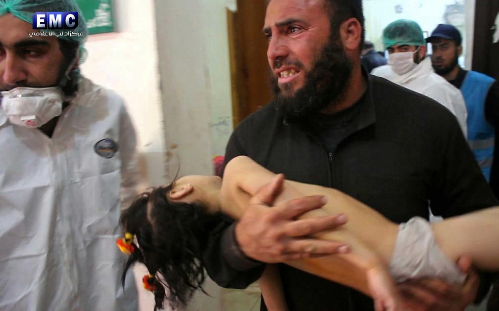 Homem socorre criança após ataque químico em Idlib, no norte da Síria, nesta terça-feira (4)  (Foto: Edlib Media Center, via AP)