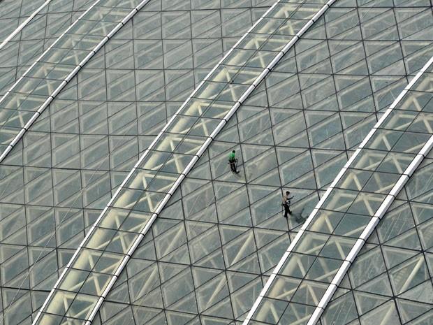 """Funcionários limpam vidraça do """"New Century Global Centre"""" (Foto: STR/AFP)"""