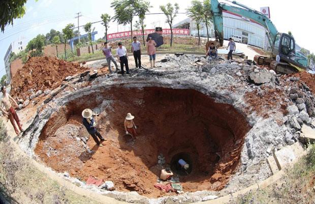 Equipes de resgate trabalham no local em que grande buraco se abru nesta terça-feira (18) na China (Foto: China Daily/Reuters)