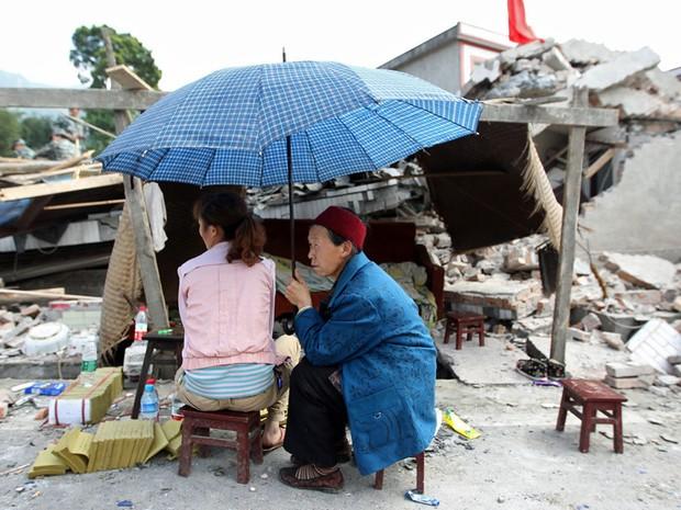 População acompanha resgate de vítimas ao lado de um edifício Sichuan (Foto: AFP)