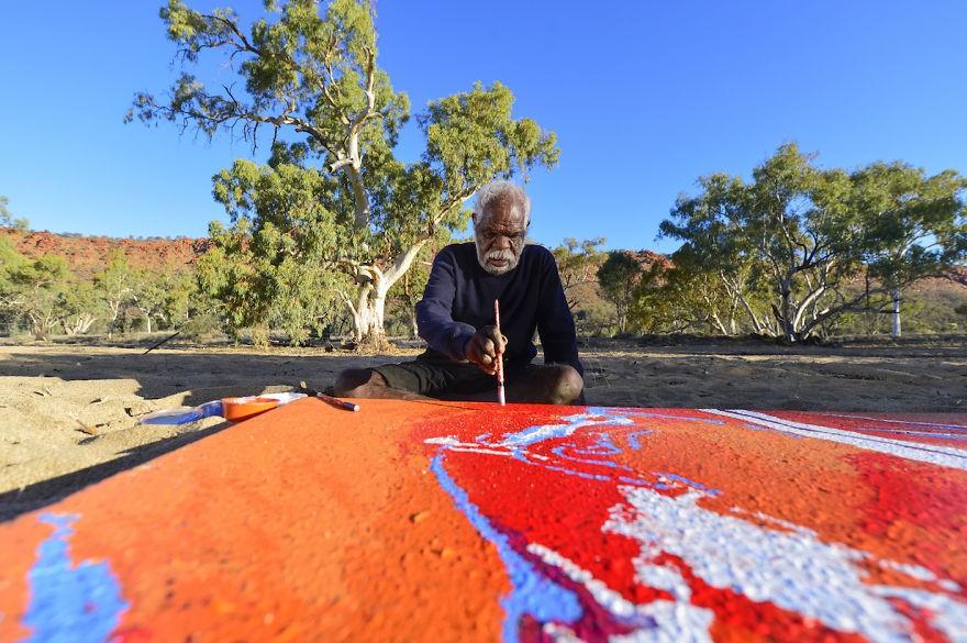 O indígena Yannima Tommy Watson, um dos maiores nomes da arte contemporânea da Austrália, não gosta de estúdios, prefere pintar ao ar livre. (Foto: Reprodução)