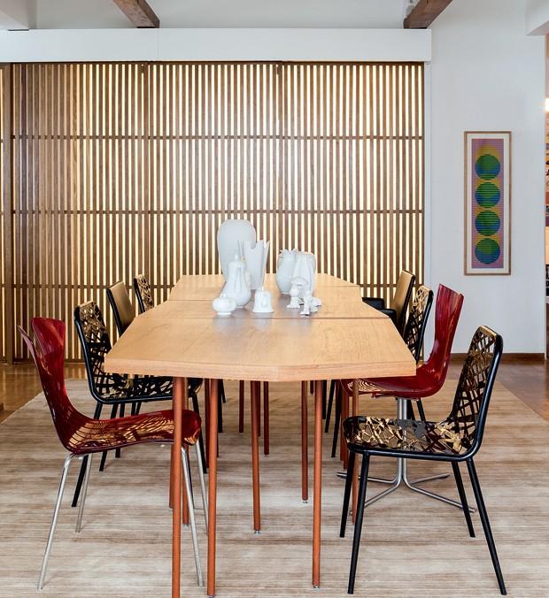 Traçada por Thiago, a mesa modular tem louças da Loja Teo e L'Oeil. Cadeiras vermelhas da A Lot Of. Tapete da Abade. A porta ripada da cozinha e as vigas junto ao teto, de cumaru, foram feitas pela Marcenaria Lanzili. Na parede, obra de Carlos Cruz-Diez, da Arterix (Foto: Lufe Gomes/Editora Globo)