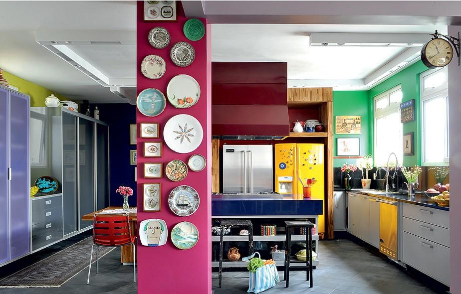 A mistura improvável de cores e a integração com a sala norteou a concepção da cozinha. A moradora é apaixonada por cores e chamou a arquiteta Tieko Matsuda. Somente a coluna estrutural foi mantida e recebeu a cor fúcsia e a coleção de pratos