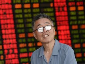 Um investidor de ações olha para cima em uma corretora de Xangai, na China. O país cortou a taxa de juros pela 4ª vez para impulsionar a economia que deve ter o pior crescimento em 25 anos (Foto: Chinatopix/via AP)