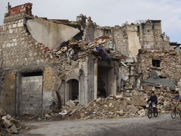 Meninos andam de bicicleta perto de um edifício danificado no bairro de Bab al-Nasr de Aleppo, na Síria (Foto: Hosam Katan/Reuters)
