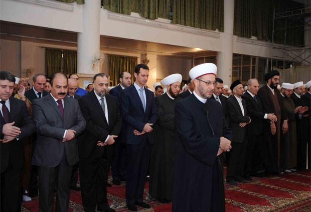 Em uma fotografia publicada em sua conta oficial no Twitter, Assad aparece rezando ao lado do primeiro-ministro Wael Halaqi e do grande mufti Ahmed Badreddin Hasun (Foto: Reprodução/Twitter/Syrian Presidency)