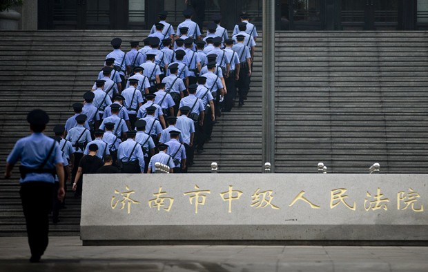 Policiais chineses fazem a segurança do Tribunal em Jinan (Foto: Andy Wong/ AP)