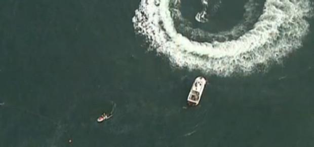 Equipes de resgate buscam os tripulantes do helicóptero do Corpo de Bombeiros que caíram no mar na praia de Copacabana, no Rio de Janeiro (Foto: Reprodução TV Globo)