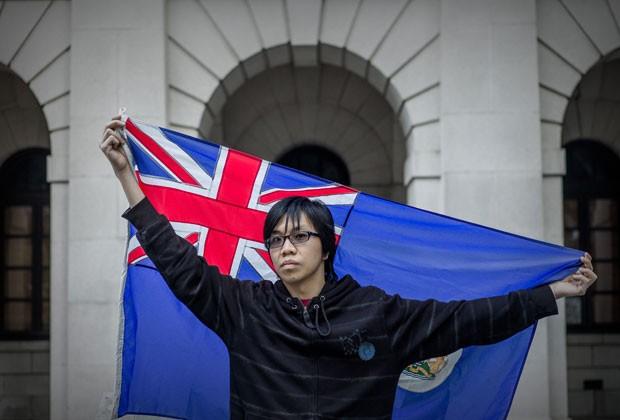 Danny Chan, de 26 anos, posa com a bandeira colonial no dia 31 de janeiro em Hong Kong (Foto: Philippe Lopez/AFP)