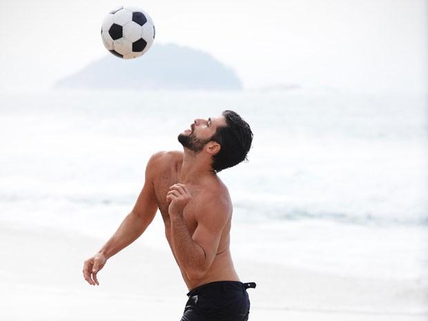 Na pele de Edu, Bruno Gagliasso joga bola na praia (Foto: Raphael Dias/TV Globo)