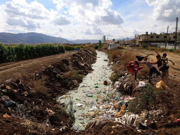 Meninos refugiados sírios jogam lixo no esgoto aberto de um campo de refugiados em  Hosh Hareem, no Líbano. Segundo a Organização das Nações Unidas o conflito na Síria deixou mais de 6 milhões de crianças carentes de ajuda e alguma forma de proteção (Foto: Hassan Ammar/AP)